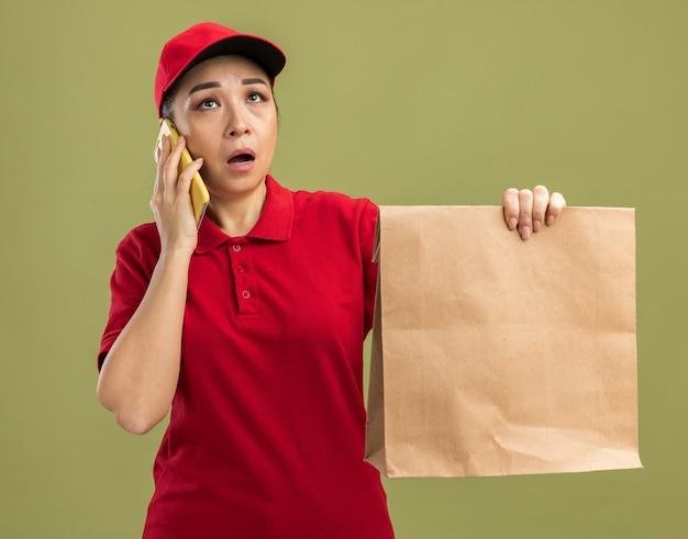 Jonge bezorger in rood uniform en pet met papieren pakket die verward en verrast kijkt terwijl ze op een mobiele telefoon praat die over een groene muur staat