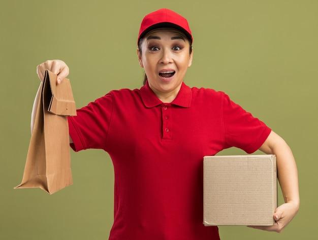 Jonge bezorger in rood uniform en pet met papieren pakket en kartonnen doos blij en verrast over groene muur