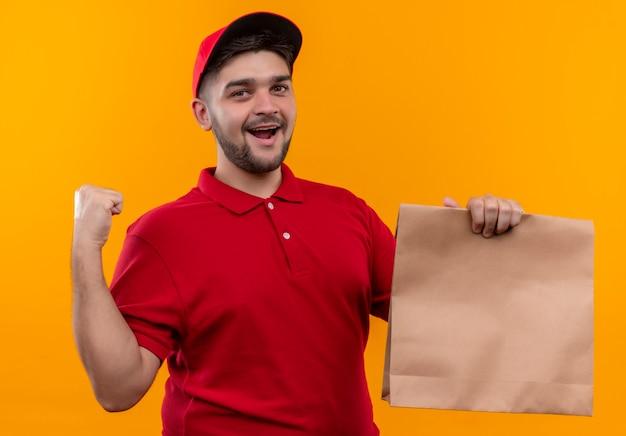 Jonge bezorger in rood uniform en pet met papieren pakket gebalde vuist blij en verlaten breed glimlachend
