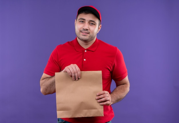 Jonge bezorger in rood uniform en pet met papieren pakket met glimlach op gezicht staande over paarse muur