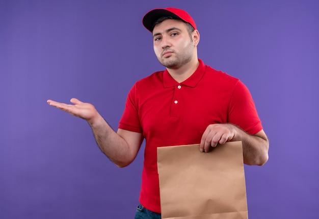 Jonge bezorger in rood uniform en pet met papieren pakket met kopie ruimte met arm van hand staande over paarse muur