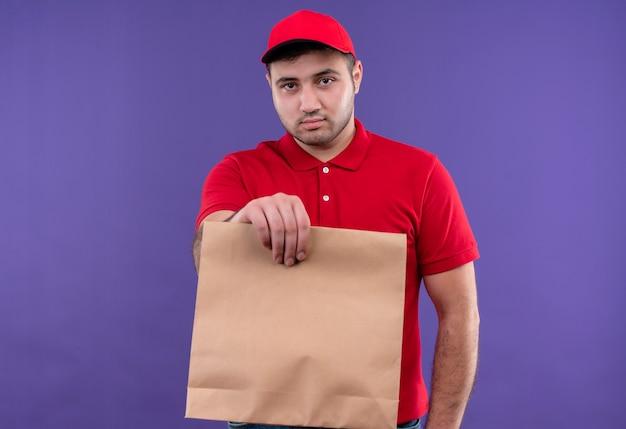 Jonge bezorger in rood uniform en pet met papieren pakket met serieus gezicht staande over paarse muur
