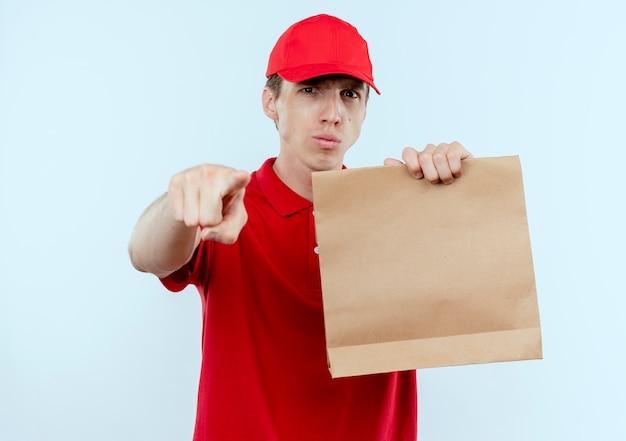 Jonge bezorger in rood uniform en pet met papieren pakket wijzend met vinger naar voren met ernstig gezicht staande over witte muur