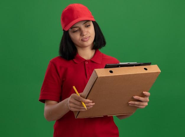 Jonge bezorger in rood uniform en pet met pizzadoos en klembord met potlood kijken naar klembord met glimlach op gezicht staande over groene muur