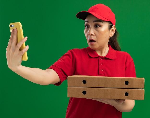 Jonge bezorger in rood uniform en pet met pizzadozen die naar het scherm van haar smartphone kijkt en zich zorgen maakt over de groene muur