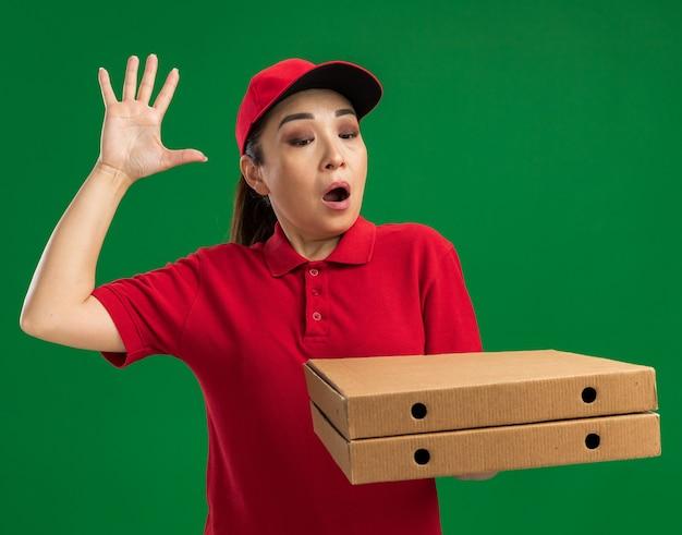 Jonge bezorger in rood uniform en pet met pizzadozen die verbaasd en verrast kijkt met opgeheven arm over groene muur