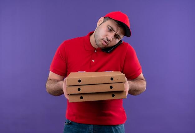 Jonge bezorger in rood uniform en pet met pizzadozen die verward kijken tijdens het praten over de mobiele telefoon die over de paarse muur staat