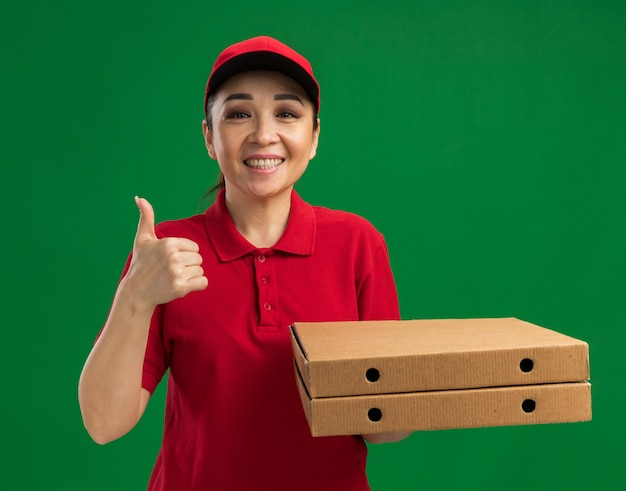 Jonge bezorger in rood uniform en pet met pizzadozen die vriendelijk glimlachen en duimen omhoog laten staan over groene muur