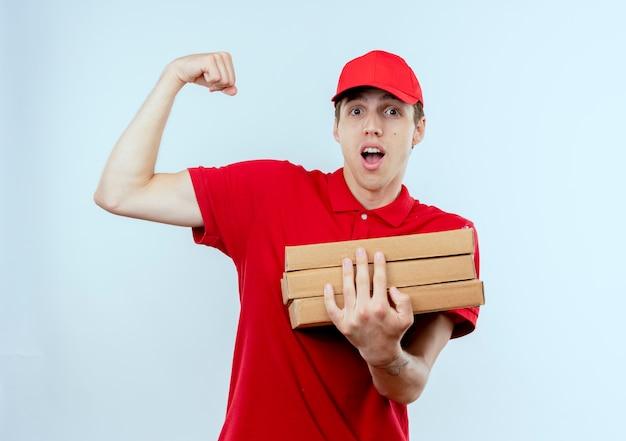 Jonge bezorger in rood uniform en pet met pizzadozen die vuist opheffen die emotionele en gelukkige biceps tonen, winnaarconcept dat zich over witte muur bevindt