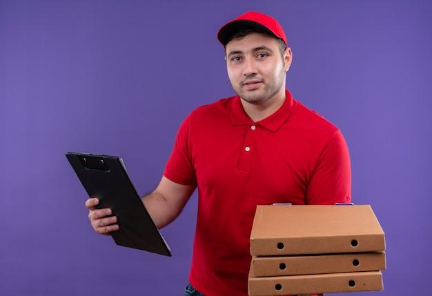 Jonge bezorger in rood uniform en pet met pizzadozen en klembord lachend met blij gezicht staande over paarse muur