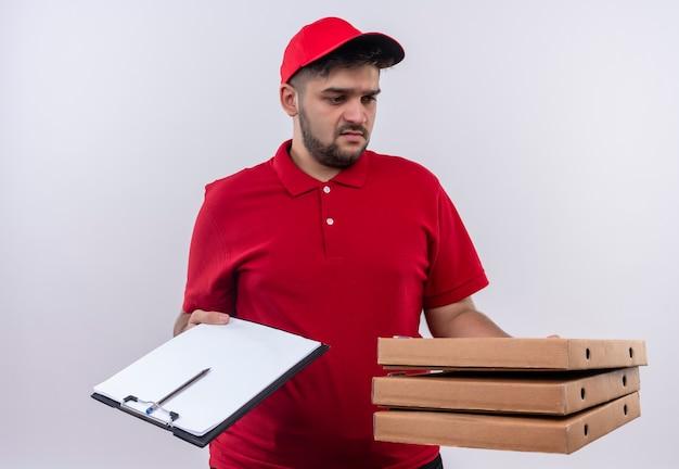 Jonge bezorger in rood uniform en pet met pizzadozen en klembord met pen en blanco pagina's op zoek verward proberen een keuze te maken
