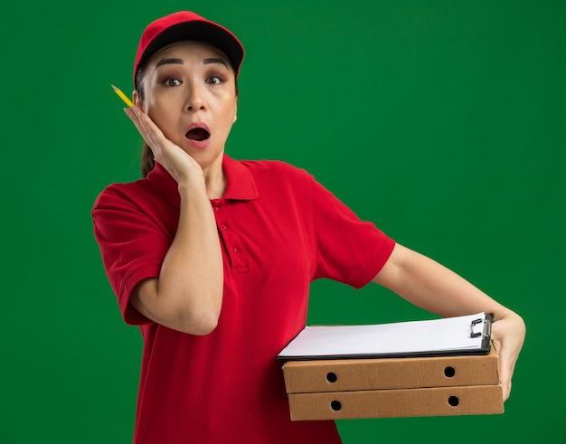 Jonge bezorger in rood uniform en pet met pizzadozen en klembord met pen verbaasd en verrast over groene muur