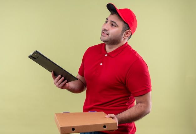 Jonge bezorger in rood uniform en pet met pizzadozen en klembord opzij kijken met glimlach op gezicht staande over groene muur