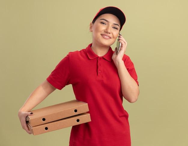 Jonge bezorger in rood uniform en pet met pizzadozen lachend met een blij gezicht tijdens het praten over de mobiele telefoon die zich over de groene muur bevindt