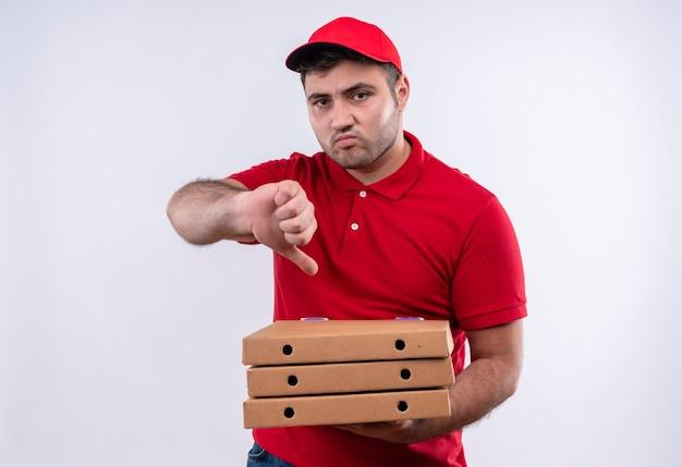 Jonge bezorger in rood uniform en pet met pizzadozen ontevreden met duimen naar beneden staande over witte muur