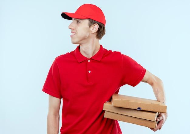 Jonge bezorger in rood uniform en pet met pizzadozen opzij kijken met zelfverzekerde uitdrukking staande over witte muur