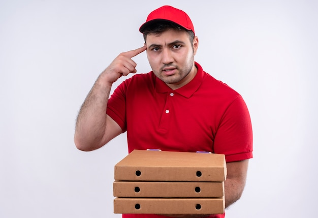 Jonge bezorger in rood uniform en pet met pizzadozen wijzend met de vinger zijn tempel op zoek zelfverzekerd gericht op een taak die over een witte muur staat