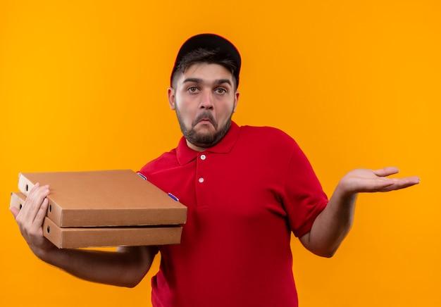 Jonge bezorger in rood uniform en pet met stapel pizzadozen die er onzeker en verward uitzien, arm opheffen zonder antwoord