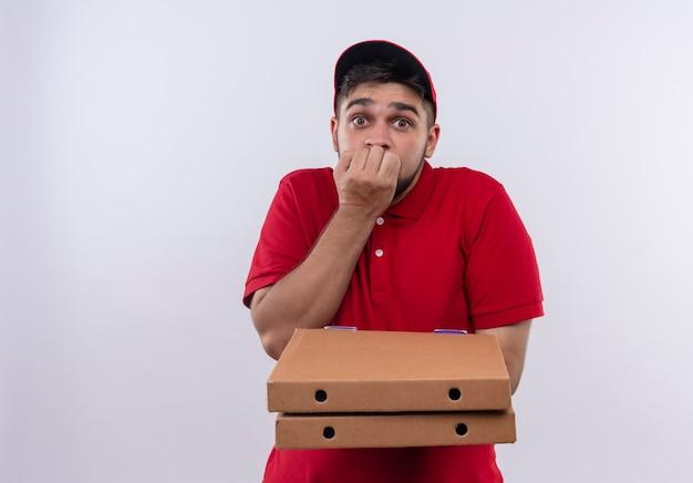 Jonge bezorger in rood uniform en pet met stapel pizzadozen geschokt en bang nagels bijten