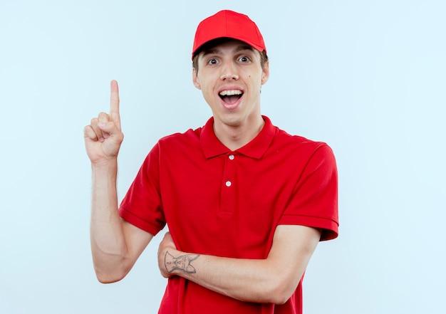 Jonge bezorger in rood uniform en pet met wijsvinger met nieuw idee blij en opgewonden staande over witte muur
