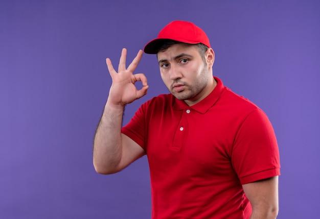 Jonge bezorger in rood uniform en pet met zelfverzekerde uitdrukking ok doen zingen staande over paars