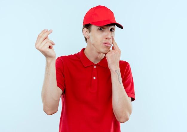 Jonge bezorger in rood uniform en pet naar voren kijken vingers wrijven vragen om geld wijzend met vinger naar zijn oog wachten op betaling staande over witte muur