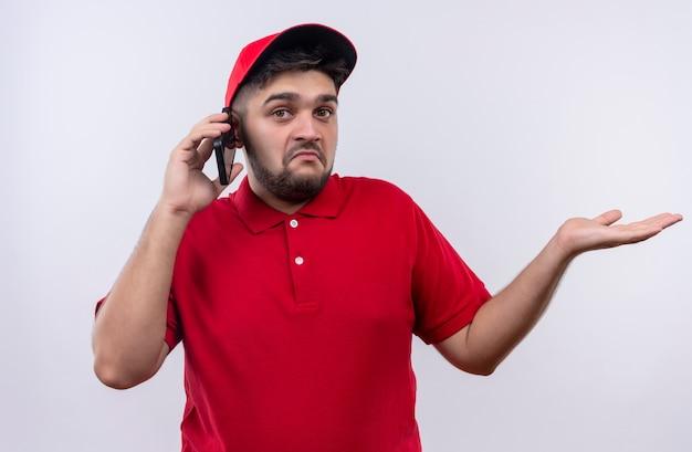 Jonge bezorger in rood uniform en pet op zoek verward tijdens het praten op de mobiele telefoon
