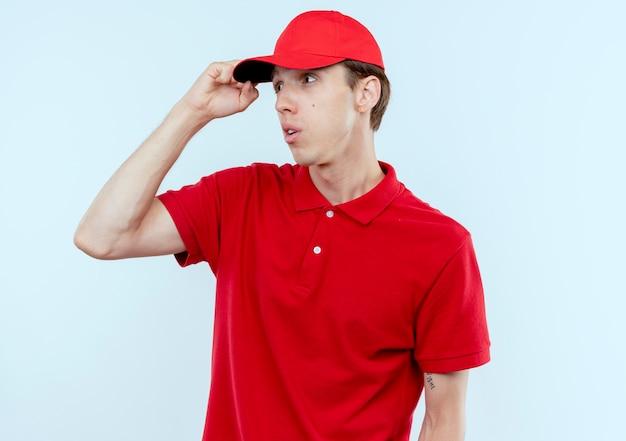 Jonge bezorger in rood uniform en pet opzij kijken verward met hand oh zijn hoofd staande over een witte muur