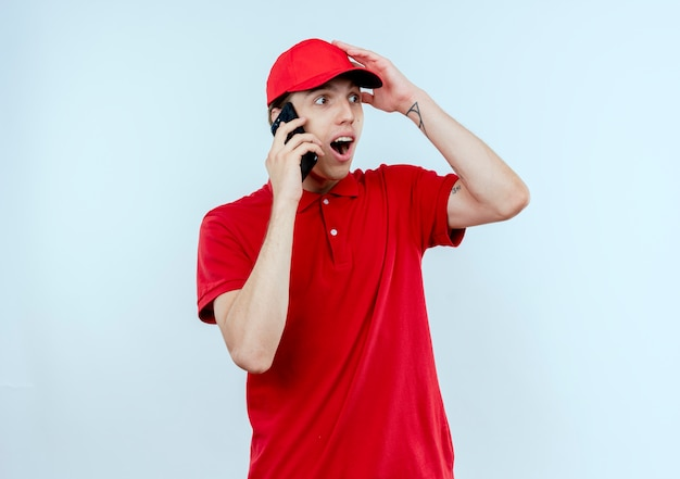 Jonge bezorger in rood uniform en pet praten op mobiele telefoon op zoek verrast en verbaasd staande over de witte muur