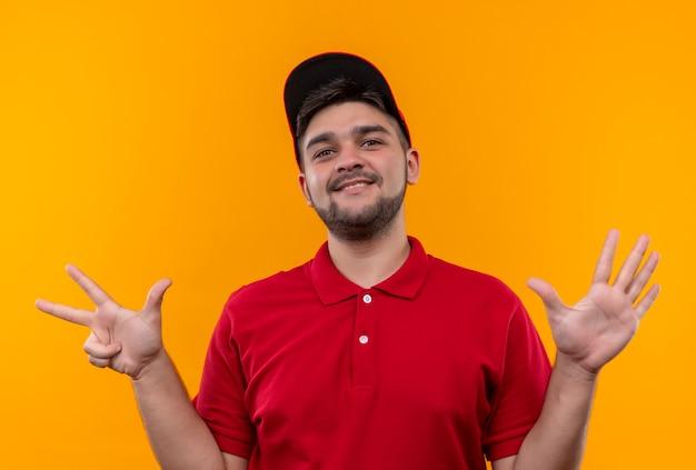 Jonge bezorger in rood uniform en pet tonen en omhoog met vingers nummer acht, glimlachend