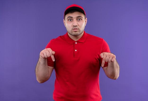 Jonge bezorger in rood uniform en pet wijzend met wijsvingers naar beneden kijkend verrast staande over paarse muur