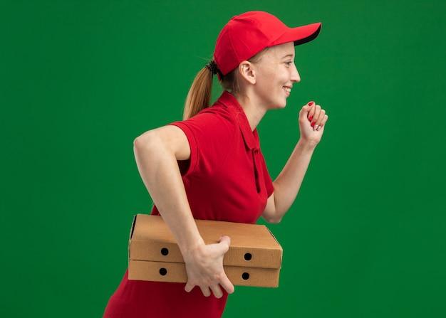 Jonge bezorger in rood uniform en petje rennend voor het bezorgen van pizzadozen voor de klant