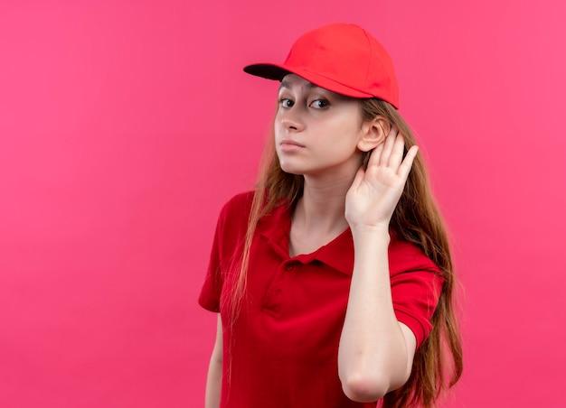 Jonge bezorger in rood uniform kan je niet horen op geïsoleerde roze muur met kopie ruimte