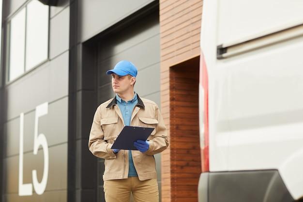 Jonge bezorger in uniform werken met ladingen in magazijn buitenshuis