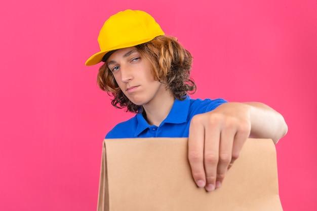 Jonge bezorger met blauw poloshirt en gele pet met papieren pakket in handen kijkend naar camera met scepticus en nerveus staande over geïsoleerde roze achtergrond