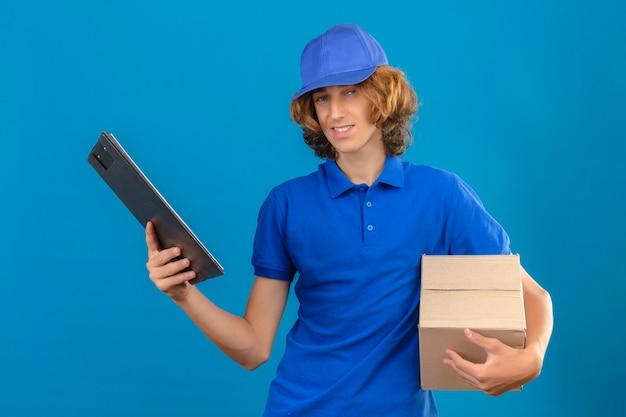 Jonge bezorger met blauw poloshirt en pet met pizzadoos en klembord met lege plekken terwijl glimlachend vriendelijk staande met blij gezicht over geïsoleerde blauwe achtergrond