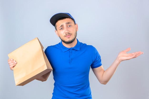 Jonge bezorger met blauwe polo shirt en pet staan met papieren pakket met afhaalmaaltijden verward met opgeheven handen over geïsoleerde witte achtergrond