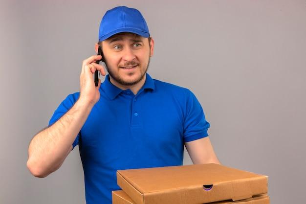 Jonge bezorger met een blauw poloshirt en een pet die stapel pizzadozen vasthoudt terwijl hij aan het praten is op de mobiele telefoon en kijkt nerveus en verward over geïsoleerde witte achtergrond