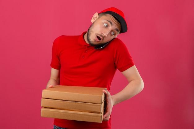 Jonge bezorger met een rood poloshirt en een pet die zich met een stapel pizzadozen bevindt terwijl hij op zijn mobiele telefoon praat en verbaasd kijkt over geïsoleerde roze achtergrond