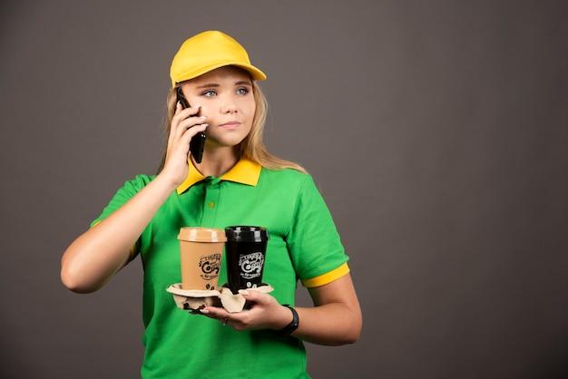 Jonge bezorger met kopjes koffie spreken op smartphone.