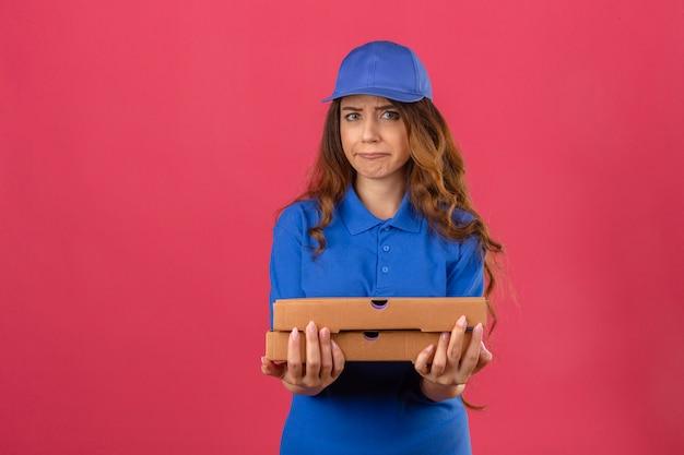 Jonge bezorger met krullend haar die een blauw poloshirt en een pet draagt die zich met pizzadozen met ongelukkig droevig gezicht gaat huilen over geïsoleerde roze achtergrond