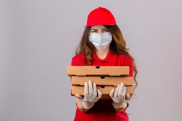 Jonge bezorger met krullend haar dragen rode poloshirt en pet in medisch beschermend masker en handschoenen staan met pizzadozen sceptisch en nerveus fronsen boos vanwege probleem over isola