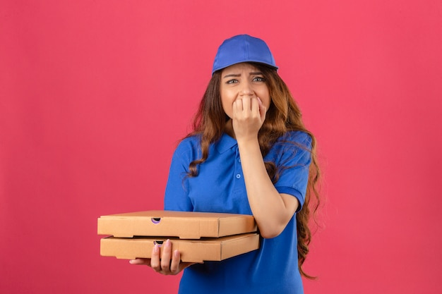 Jonge bezorger met krullend haar gekleed in een blauw poloshirt en een pet staan met pizzadozen op zoek gestrest en nerveus met handen op mond nagels bijten over geïsoleerde roze achtergrond