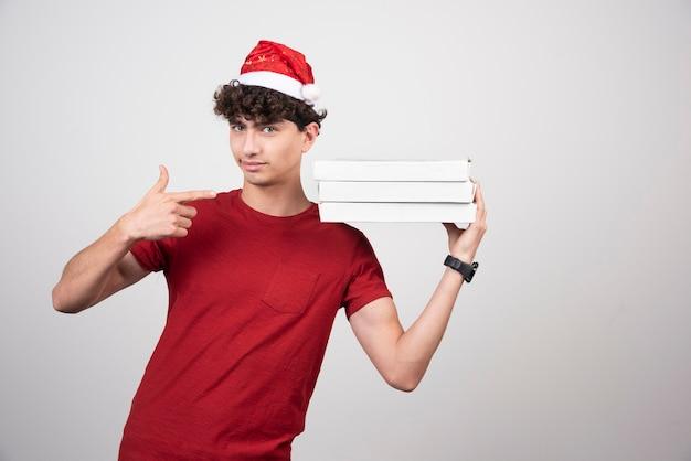 Jonge bezorger met pizzadozen die duimen opgeven