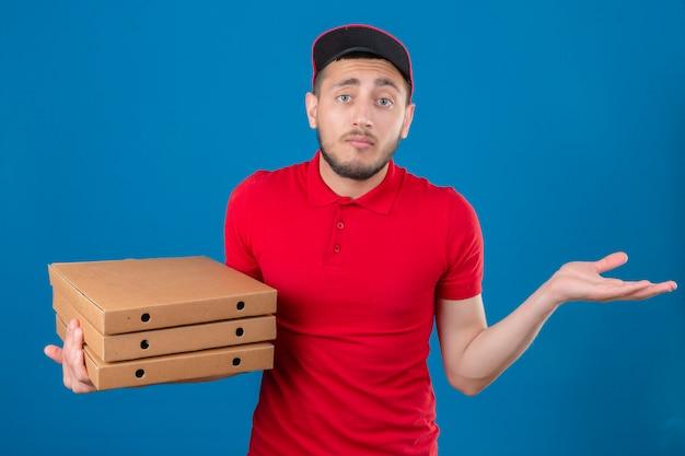 Jonge bezorger met rode polo shirt en pet schouderophalend en open ogen verward over geïsoleerde blauwe achtergrond