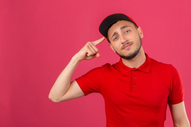 Jonge bezorger met rode polo shirt en pet wijzende tempel met vinger denken gericht op een taak over geïsoleerde roze achtergrond