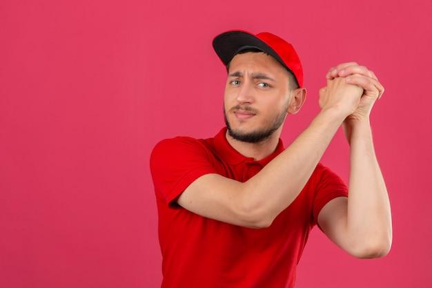Jonge bezorger met rood poloshirt en pet gebaren met gevouwen op zoek zelfverzekerd en trots op geïsoleerde roze achtergrond