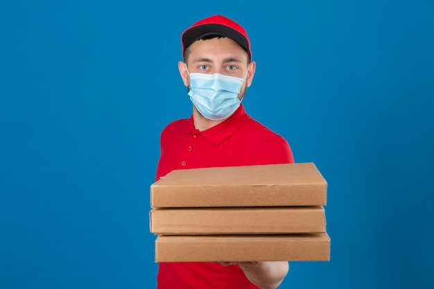 Jonge bezorger met rood poloshirt en pet in beschermend medisch masker uitrekken van een stapel pizzadozen camera kijken met ernstig gezicht over geïsoleerde blauwe achtergrond