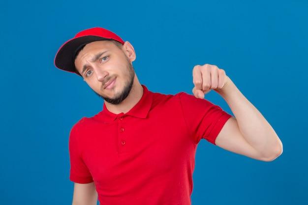 Jonge bezorger met rood poloshirt en pet kijkt naar camera glimlachend vriendelijk gebaren vuist hobbel alsof begroeting goedkeurend of als teken van respect over geïsoleerde blauwe achtergrond