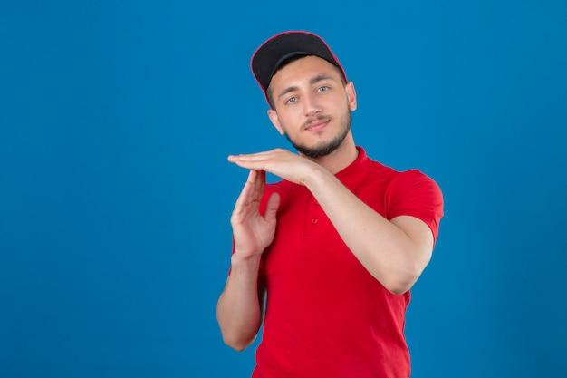 Jonge bezorger met rood poloshirt en pet op zoek overwerkt maken time-out gebaar met handen over geïsoleerde blauwe achtergrond